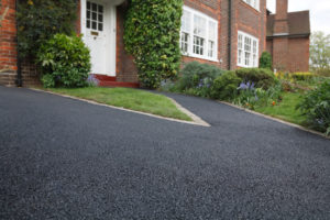 house driveway with black asphalt sealcoat. protective layer. southern maryland excavating.